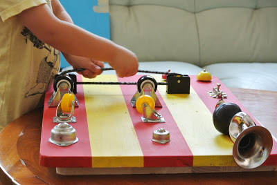 toddler is playing with red and yellow sensory board, that has some wheels and horn on it.